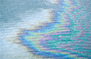 Alaska. Colorful sheen show oil spill's movement at sea.