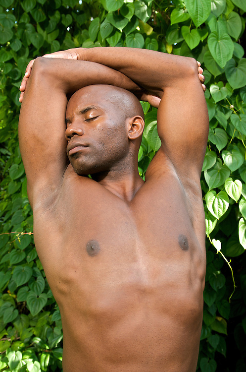 A young african american relaxes while practicing yoga in a natural environment.
