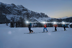 Ski mountaineers climbing on snowy mountain with head torches, Val Gardena, Trentino-Alto Adige, Italy