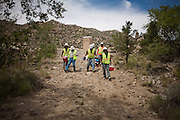 The construction crew walk down a hill to collect their pay after another week at work on the Carnuel Water Systems Improvement Project on Friday August 27, 2010. The $3.4 million project is supported by $2 million from the American Recovery and Reinvestment Act and will provide clean water to hundreds of Bernalillo County residents.