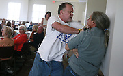 Ed, center, who declined to give his last name, scuffles with Ron Eid, right, after Ed took the mic, and refused to give it up after making remarks against Islam and muslims during a conversation about immigration and refugees  organized by the United Methodist Women and held at the Bloomington First United Methodist Church. (Photo by Jeremy Hogan)