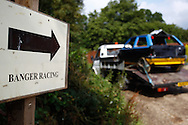 The sign points the way as a competitor enters the circuit with their race car strapped to the back of their low loader during the race meeting at Smallfield Raceway, Surrey, UK on the 10th of July 2011 (photo by Andrew Tobin/SLIK images)