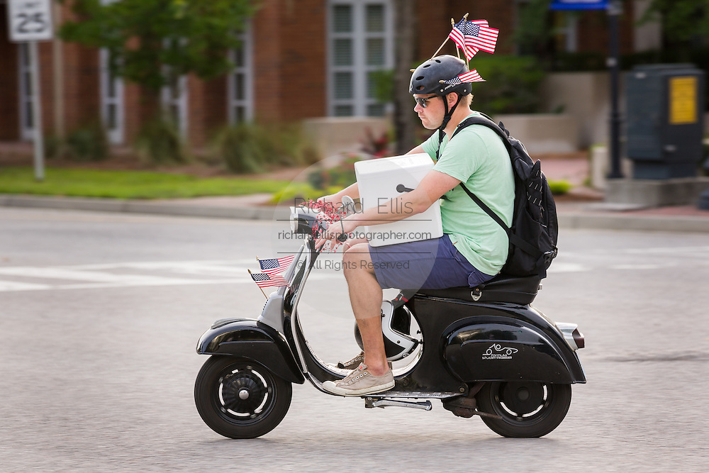 A man carrying a cooler on his scooter rides decorated with American flags during the Daniel Island Independence Day parade July 3, 2015 in Charleston, South Carolina.