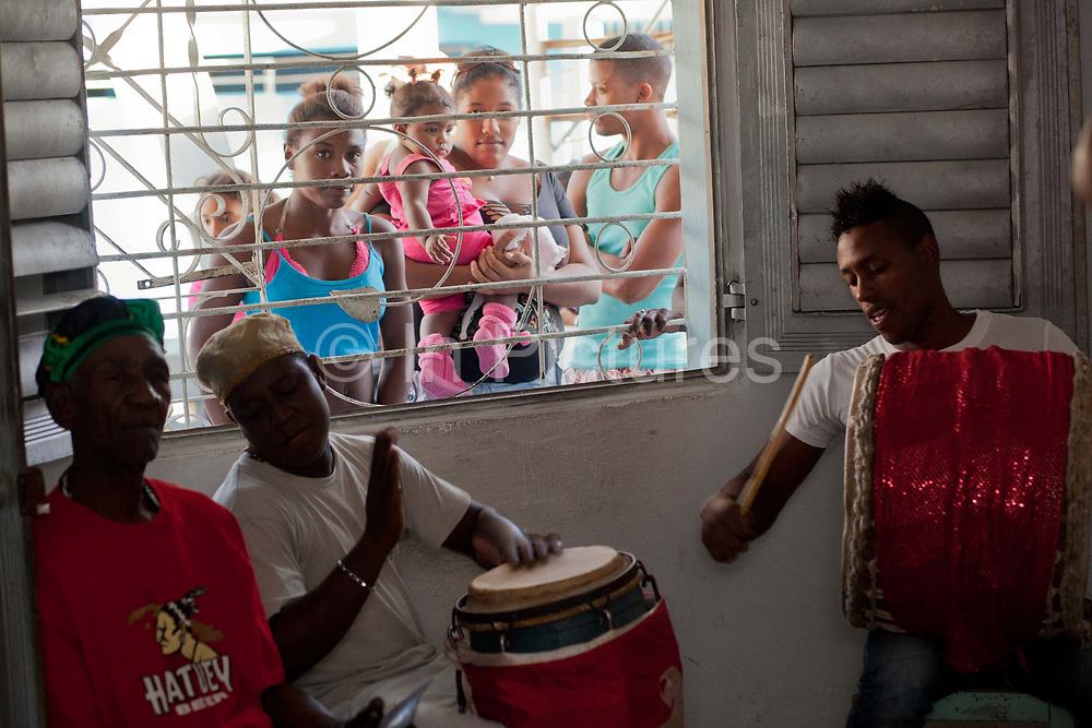 Young afro-Cuban men playing drums as part of a Santeria ceremony. Santeria is a syncretic religion practiced in Cuba, it is a mixture of Yoruba tribal practices brought from Nigeria during Colonial times, and traditional Catholic beliefs. During this time, the slaves used the images of saints to cover up their worship of the Orishas (spirits).