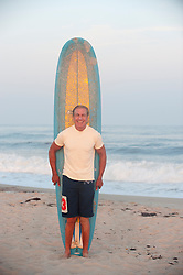 Older man with a surfboard at the ocean