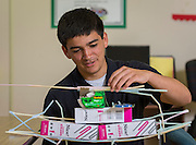 Recent graduate Moses Navarro works on the load tolerance of a straw bridge during in a summer intern program with FH-HP at Washington High School, June 16, 2014.
