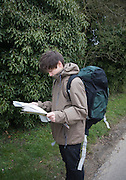 Model released young man hiker map reading