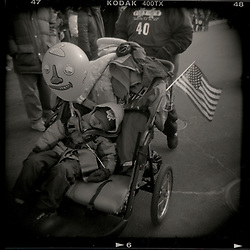 A young boy in a stroller sits asleep before the parade at the Chinese New Year Parade held annually in Washington, DC's Chinatown. A smiley faced balloon and an American flag adorn his stroller...