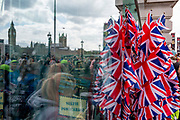 British Union Jack flags on sale at the London Eye and the reflection of the Houses of Parliament at Westminster, on 20th July 2017, on the Southbank, London, England.