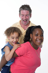 Woman giving a young boy a piggy back while man looks on; laughing,