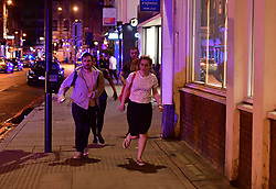 """People run down Borough High Street as police are dealing with a """"major incident"""" at London Bridge."""