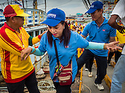 """23 JUNE 2015 - MAHACHAI, SAMUT SAKHON, THAILAND: People get off a fishing boat during the procession for the City Pillar Shrine in Mahachai. The Chaopho Lak Mueang Procession (City Pillar Shrine Procession) is a religious festival that takes place in June in front of city hall in Mahachai. The """"Chaopho Lak Mueang"""" is  placed on a fishing boat and taken across the Tha Chin River from Talat Maha Chai to Tha Chalom in the area of Wat Suwannaram and then paraded through the community before returning to the temple in Mahachai.   PHOTO BY JACK KURTZ"""
