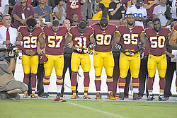 """Washington Redskins team president Bruce Allen, far left, locks arms in solidarity with players, from left to right, cornerback Kendall Fuller (29), long snapper Nick Sundberg (57), cornerback Fabian Moreau (31), nose tackle Ziggy Hood (90), defensive end Jonathan Allen (95), and outside linebacker Martrell Spaight (50) as the national anthem is sung prior to the game against the Oakland Raiders at FedEx Field in Landover, Maryland on Sunday, September 24, 2017. The Redskins chose to demonstrate prior to their nationally televised contest following tweets earlier in the day from United States President Donald J. Trump urging owners to """"fire or suspend"""" players who participated in the protests by not standing for the anthem. Photo by Ron Sachs/CNP/ABACAPRESS.COM"""