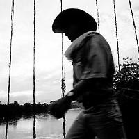 A resident of San Vicente crosses a suspension bridge over the Rio Caquan.<br />