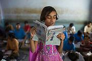 Indian girl reading aloud during English lesson at Rajyakaiya School in Narlai village, Rajasthan, Northern India