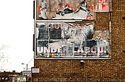 Remains of poster advertising Labour party policies on side of building. Poster has lion and warning about taxes