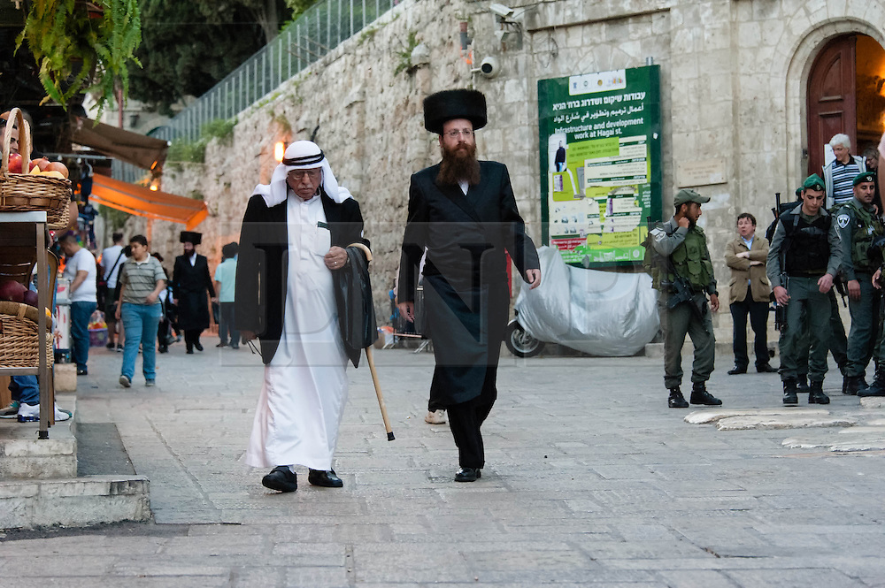 © Licensed to London News Pictures. 02/05/2014. Jerusalem, Israel. A jew hurries past an arab through the Muslim Quarter of the Old City of Jerusalem at approx 6.30pm in order to reach The Western Wall  in time for the start of the Shabbat (the Jewish sabbath).  Armed police stand nearby.  Jewish custom sees the lighting of candles scheduled for 6.39pm this evening, shortly before the sunset when Shabbat commences.  The Western Wall is the most important shrine of the Jewish faith and is located in the Old City at the foot of the western side of Temple Mount.  The Old City is comprised of four Quarters - the Jewish, Muslim, Christian and Armenian. Photo credit : Richard Isaac/LNP