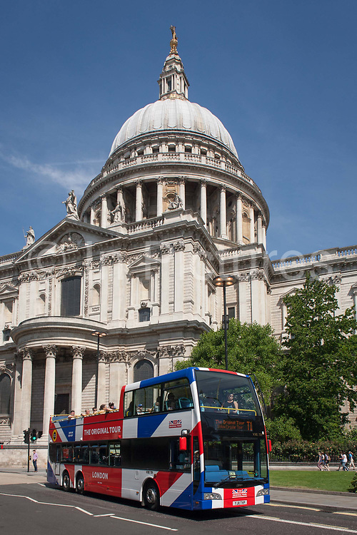 A tour bus with The Original Tour latest branding of a Union jack flag drives past the Sir Christopher Wren-designed St. Pauls Cathedral, on 7th July 2017, in central London.