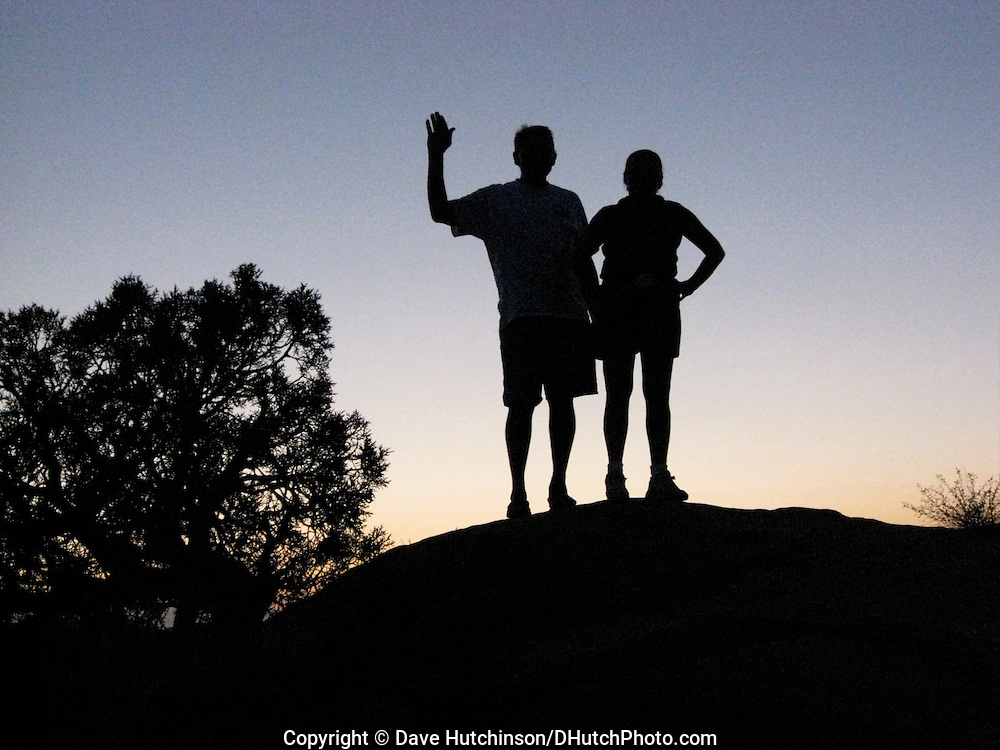 Happy Trails.  Friends waving, silhouetted against sky at dusk.