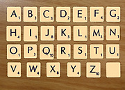 Digitally created image of a full alphabet of scrabble tiles on a wooden background