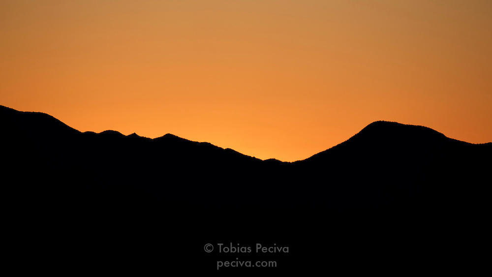 Orange sunset behind a dark ridge in Saguaro National Park, near Tucson, Arizona.