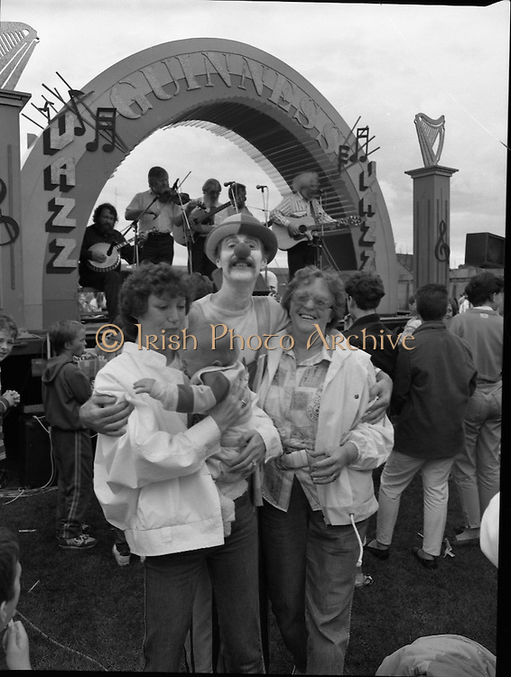 """Guinness Family Day At The Iveagh Gardens. (R83)..1988..02.07.1988..07.02.1988..2nd  July 1988..The family fun day for Guinness employees and their families took place at the Iveagh Gardens today. Top at the bill at the event were """"The Dubliners"""" who treated the crowd to a performance of all their hits. Ireland's penalty hero from Euro 88, Packie Bonner, was on hand to sign autographs for the fans...Image shows the crowd enjoying the show being put on by the Dubliners at the Family Day out though the noise seems too much for this little one."""
