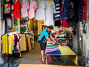 24 AUGUST 2018 - GEORGE TOWN, PENANG, MALAYSIA: A woman sets out clothes in her shop across the street from Chowrasta Market in central George Town. Chowrasta Market was originally built in 1890 and is the older of two traditional markets in George Town. The original building was torn down and replaced with a modern building in 1961 and has been renovated several times since.     PHOTO BY JACK KURTZ