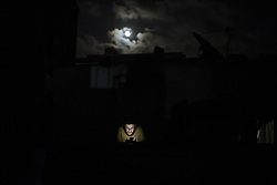 July 31, 2018 - Gaza, Gaza Strip, Palestine - A Palestinian man seen carrying a mobile phone in front of his house during a power cut in the Jabalya refugee camp in the northern Gaza Strip. Most Palestinians in the Gaza Strip use batteries, generators or candles to light their homes during blackout. (Credit Image: © Mahmoud Issa/SOPA Images via ZUMA Wire)