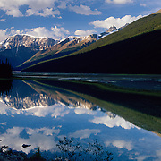 The mighty Canadian Rockies reflect in tranquil Studfield Lake in Jasper National Park, Alberta, Canada.