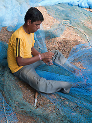 Man sitting mending fishing net, Chapora, Goa.