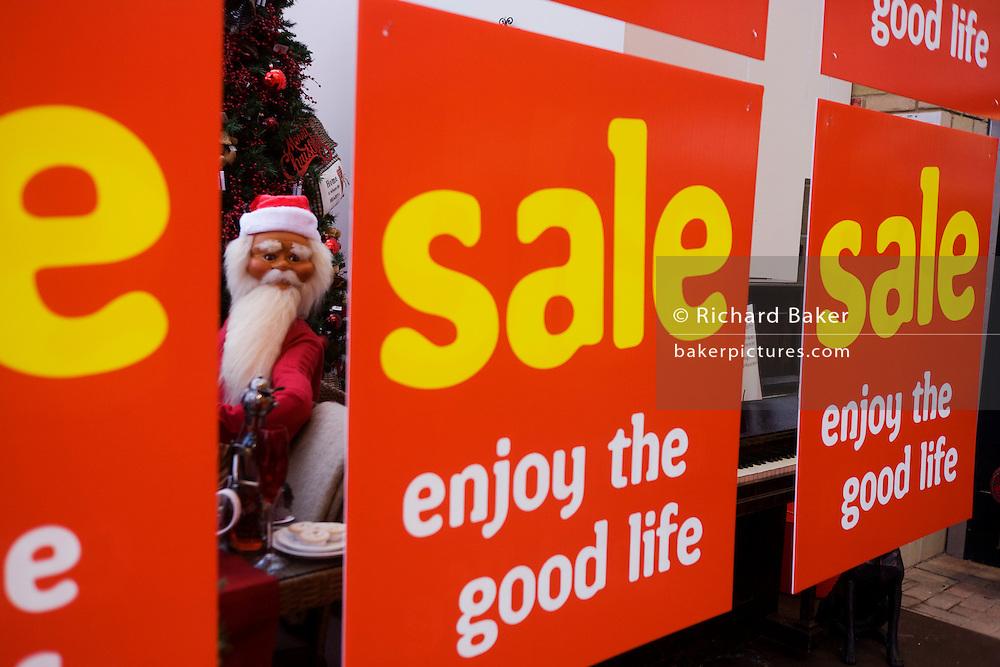 Mannequin of Santa Claus peers between Sale signs in garden retail centre in north Somerset.