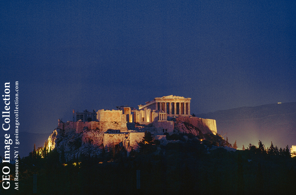 View of the Acropolis illuminated at night.