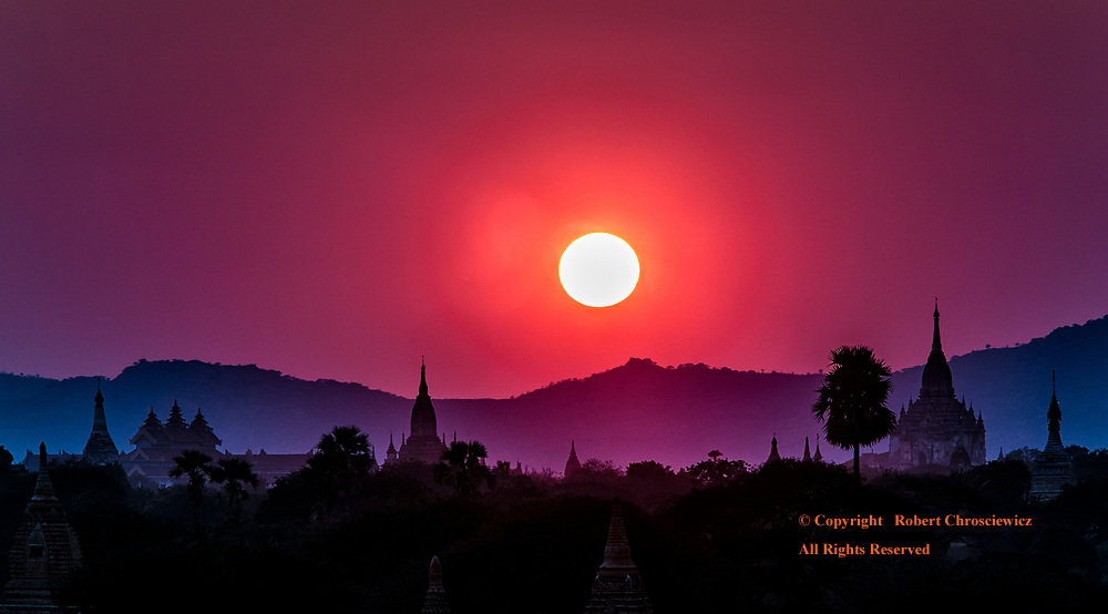 Pink to Purple: A beautiful pink and purple sky embraces the silhouettes of the ruined Buddhist Temples and Stupas, Bagan Myanmar.