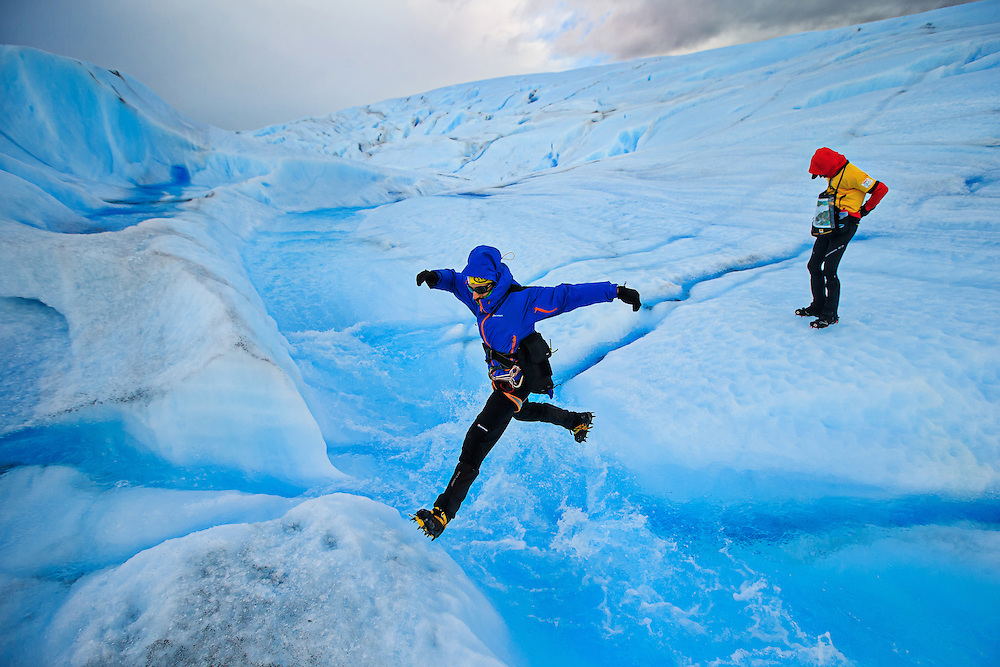 Mountain adventure photographer Alexandre Buisse leaps an ice river on Glacier Tyndall in Chilean Patagonia while following Team NorCal (USA) during the 2013 Patagonian Expedition Race.