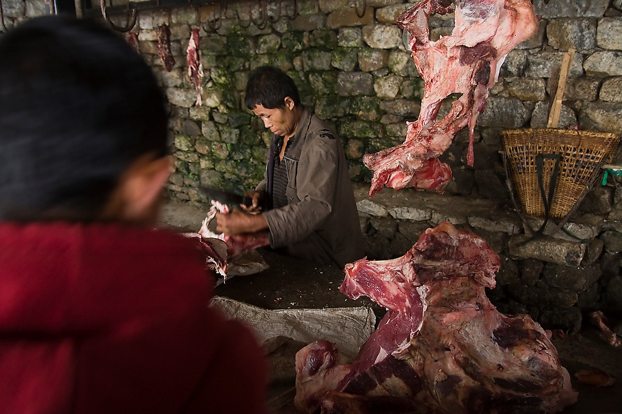 Meat on sale inside the butcher stall at the Saturday market in Namche Bazaar,  Khumbu (Everest region), Sagarmatha National Park, Himalaya Mountains, Nepal.
