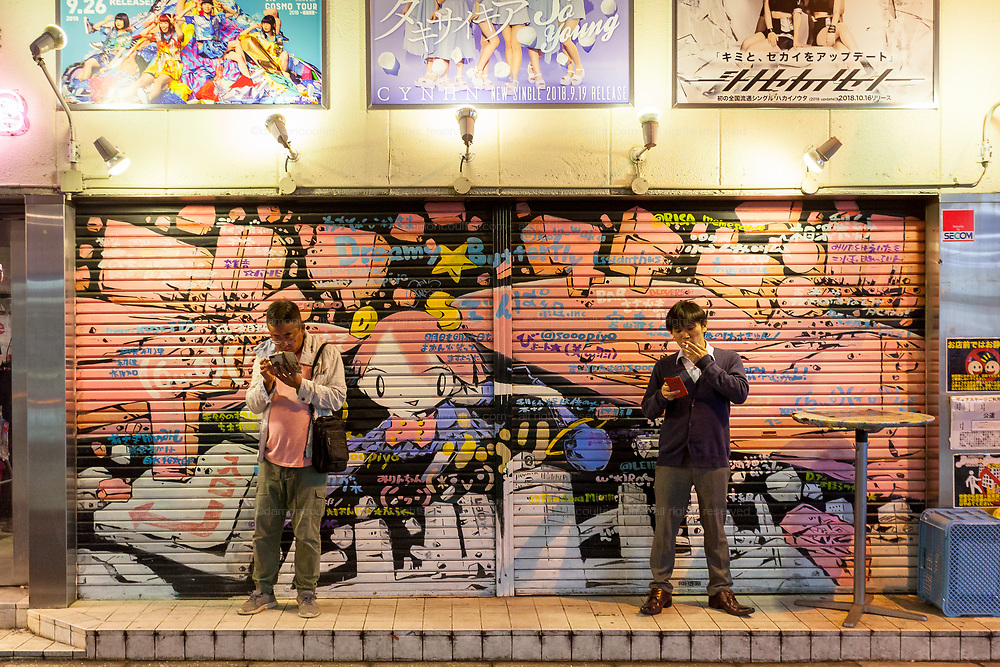 men smoking and using smart phones in front of a painted shutter in a backstreet of Akihabara, Tokyo, Japan. Friday October 19th 2018