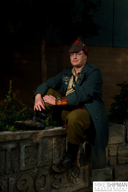Man dressed as a steampunk captain wearing a pea coat, Russian wool cap, and wrist guard, sits on a stone wall