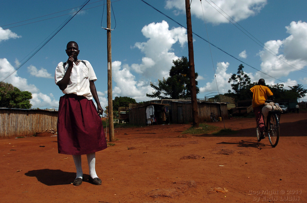 A girl walks home from school in Gulu, north Uganda on October 5, 2006. Gulu is the main base for the UPDF, Uganda Peoples Defense Force, to fight the LRA, Lord's Resistance Army. Since the war began in 1987 over 2 million people have moved from their village homes to camps close to the town of Gulu where they can be protected from the LRA by the UPDF. Over the years the LRA are said to have abducted more than 30,000 children for use as soldiers in their army. The children were often tortured and girls were frequently used as sex slaves. Current peace talks between the Ugandan government and the LRA taking place in Juba, southern Sudan, have the north Ugandan community hoping for an end to the 20 year long war..Photo by Erin Lubin