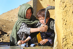 Zainab aged 9  Years old   and Hassan 4  Years old wash their hands from a standpipe which is part of a wider gravity flow drinking water system and WASH project supported by NCA, Falalij   Village Daikundi, Afghanistan.