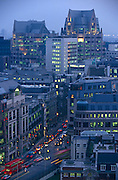 Lit offices and blurring traffic are seen at dusk from an aerial viewpoint overlooking a road junction at Aldgate
