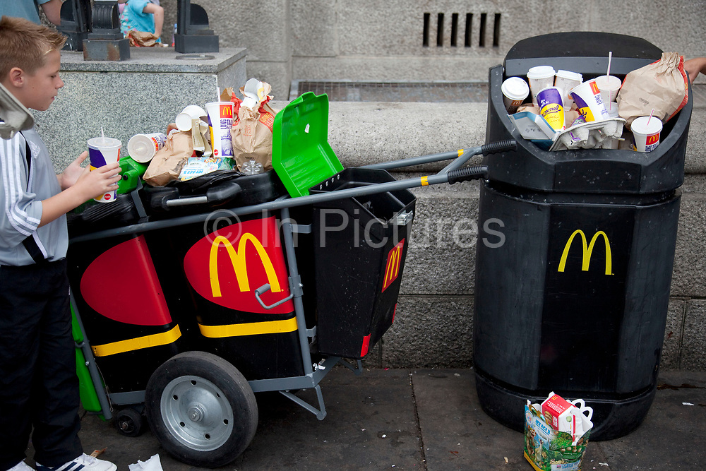 Overflowing bins full of rubbish, waste from a nearby MacDonalds fast food store. At Waterloo, the tourists flock in huge crowds, buying junk food from MacDonalds. Trahs is everywhere. Here, a MacDonalds branded waste truck lies full.