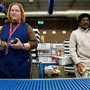 Nederland Rotterdam 11 december 2007 .Werknemers van Roteb Impact stellen kerstpaketten samen en pakken deze in aan de lopende band. Werknemers wachten tot er een volgende door over de loopband langskomt om hun onderdeel van het kerstpakket hier in te plaatsen.  Roteb Impact is een sociale werkplaats voor minder validen en geestelijk gehandicapten. ..Roteb heeft banen voor mensen die door psychische, lichamelijke of verstandelijke beperkingen alleen kunnen werken onder aangepaste omstandigheden. Rotterdammers met een handicap en op zoek naar een baan bij Roteb Ultimade, Roteb MultiGroen, Roteb Impact of andere Roteb-onderdelen dienen zich te melden bij het dichtstbijzijnde CWI...Roteb richt zich onder meer op werkgelegenheid, arbeidsintegratie en uitvoering van de Wet sociale werkvoorziening (Wsw). Roteb biedt werk aan mensen die met psychische, lichamelijke of verstandelijke beperkingen alleen kunnen werken onder aangepast omstandigheden. Daarnaast biedt Roteb leerwerkplaatsen voor andere doelgroepen met een afstand tot de arbeidsmarkt om ze meer kans te bieden op een reguliere baan..Roteb biedt in de 4 werkbedrijven, Impact, Montaz, Ultimade en MultiGroen aangepast werk. Daarnaast werken medewerkers individueel gedetacheerd of in een werkunit op locatie bij de klant. Als het nodig is begeleidt Roteb medewerkers die willen en kunnen uitstromen naar de reguliere arbeidsmarkt..Voor zover mogelijk sluit Roteb de mogelijkheden van arbeidsgehandicapten en de vragen op de reguliere arbeidsmarkt op elkaar aan. Daardoor vinden mensen met een lichamelijke, verstandelijke of psychische beperking werk dat bij hen past. We onderhouden intensieve contacten met verwijzende instellingen, belangenorganisaties en praktijkscholen. Onze werkbedrijven hebben veel zakelijke relaties in de markten en springen in op nieuwe mogelijkheden. Zij vernieuwen hun diensten en producten in samenspraak met hun partners..Roteb divisie multibedrijven is de nieuwe naam voor de werkzaamheden van Multi