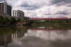 © Licensed to London News Pictures. 23/08/2012, London, UK.  A DLR train crosses over the East India Basin in east London, Thursday, Aug. 23, 2012. DLR, Docklands Light Railway, is celebrates its 25th annivesary today. Photo credit : Sang Tan/LNP