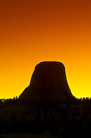 The 867 foot tall Devils Tower (a granite monolith which is a sacred site to American Indians) at sunset, Devils Tower National Monument, Wyoming USA