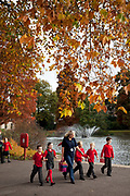 School children on a day outing during Autumn in Kew Gardens, London. Fall leaves on the many different types of trees at the Royal botanical gardens turn to yellow and brown before dropping.