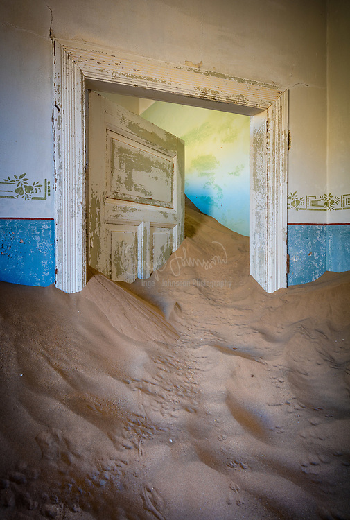 """Kolmanskop (Afrikaans for Coleman's hill, German: Kolmannskuppe) is a ghost town in the Namib desert in southern Namibia, 10 kilometres inland from the port town of Lüderitz. It was named after a transport driver named Johnny Coleman who, during a sand storm, abandoned his ox wagon on a small incline opposite the settlement. Once a small but very rich mining village, it is now a popular tourist destination run by the joint firm NamDeb (Namibia-De Beers).<br /> <br /> In 1908 the worker Zacharias Lewala found a diamond while working in this area and showed it to his supervisor, the German railway inspector August Stauch. Realizing the area was rich in diamonds, German miners began settlement, and soon after the German government declared a large area as a """"Sperrgebiet"""", starting to exploit the diamond field. Driven by the enormous wealth of the first diamond miners, the residents built the village in the architectural style of a German town, with amenities and institutions including a hospital, ballroom, power station, school, skittle-alley, theatre and sport-hall, casino, ice factory and the first x-ray-station in the southern hemisphere, as well as the first tram in Africa. It had a railway link to Lüderitz.<br /> <br /> The town declined after World War I when the diamond-field slowly exhausted and was ultimately abandoned in 1954. The geological forces of the desert mean that tourists now walk through houses knee-deep in sand."""