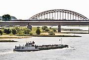 Nederland, Nijmegen, 4-6-2019 Een binnenvaartschip passeert de nevengeul in de waal ter hoogte van Nijmegen . De Waal is het Nederlandse deel van de Rijn en de belangrijkste vaarroute van en naar Rotterdam en Duitsland . Foto: Flip Franssen