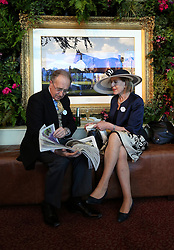Racegoers read a newspaper during day three of Royal Ascot at Ascot Racecourse.