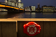 London Bridge and a life ring overlooking the Thames river on a winter's evening, on 23rd November 2018, in London, England.