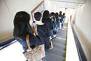 women going down an escalator inside a department store Tokyo Japan